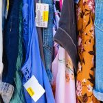 a rack of colorful clothes at Plato's